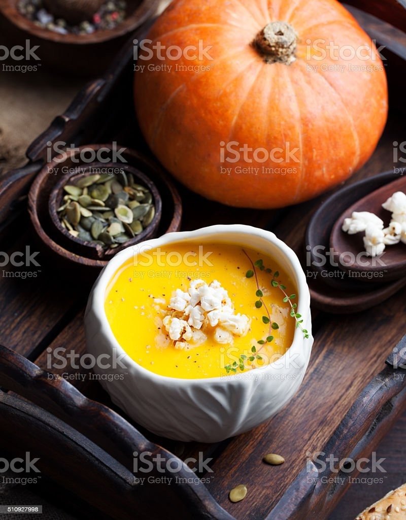 Pumpkin soup with salty popcorn in a ceramic bowl stock photo