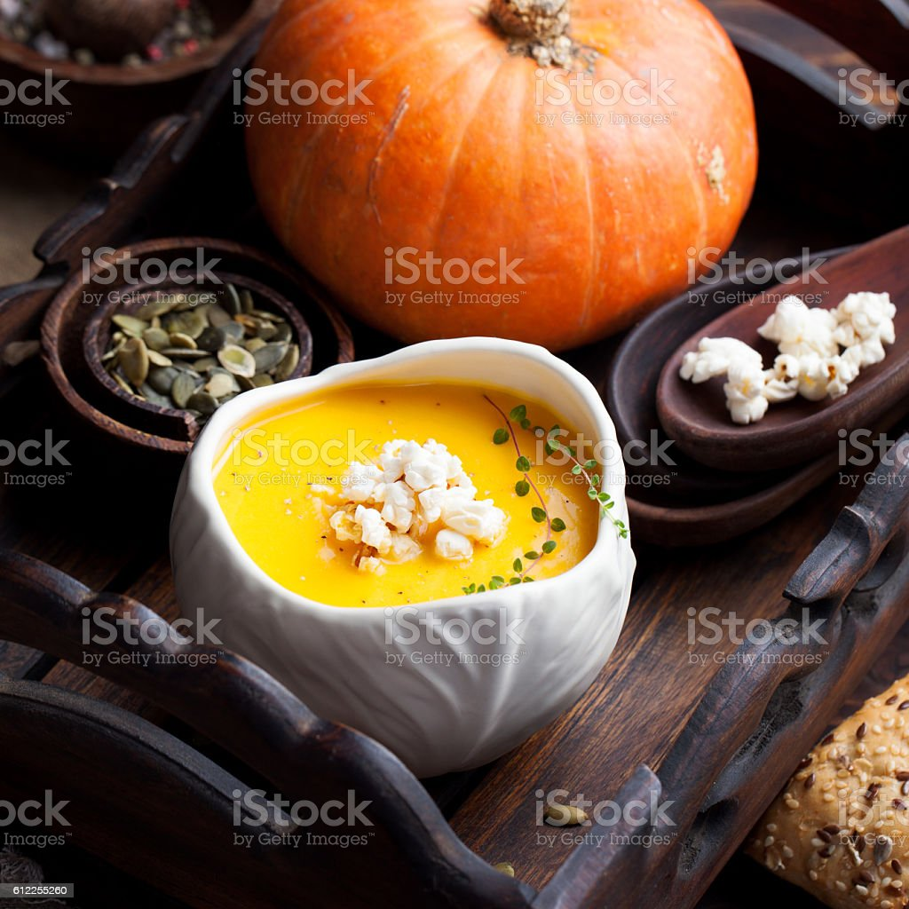Pumpkin soup with salty popcorn in a white ceramic bowl stock photo