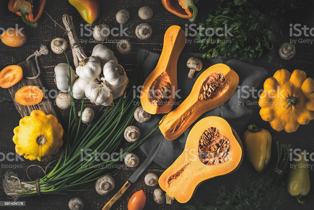 Pumpkin with different vegetables on old wooden table top view stock photo