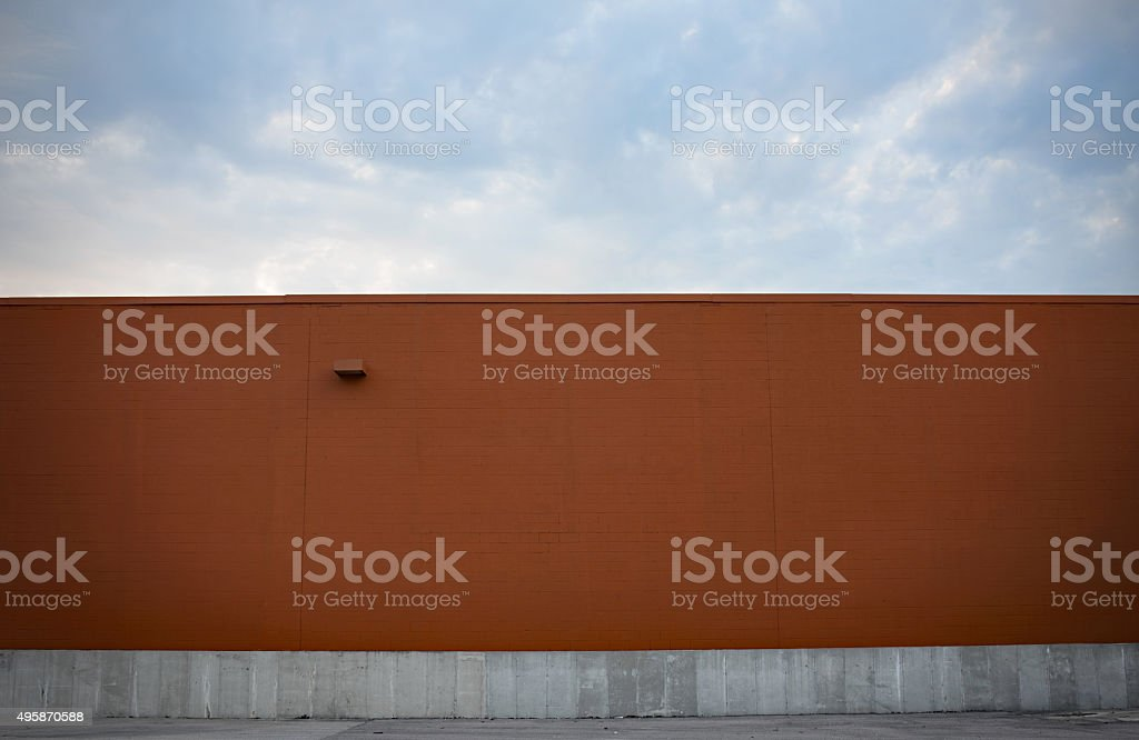 Pumpkin-colored Wall with Cloudscape stock photo