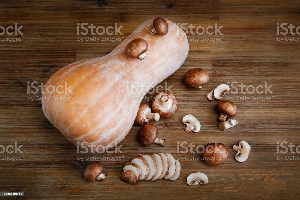 Pumpkin,Fresh Cut Mushrooms on the Wooden Table.Autumn Garden's Vegetables.Top View stock photo