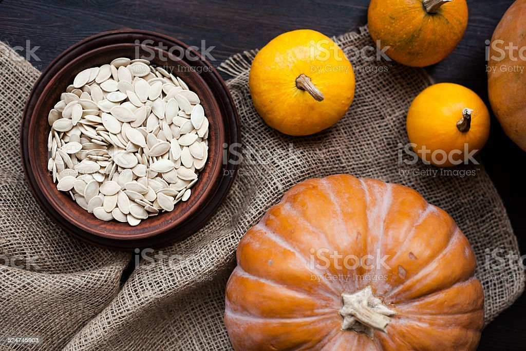Pumpkins and a bowl with toasted pumpkin seeds, wooden spoon stock photo