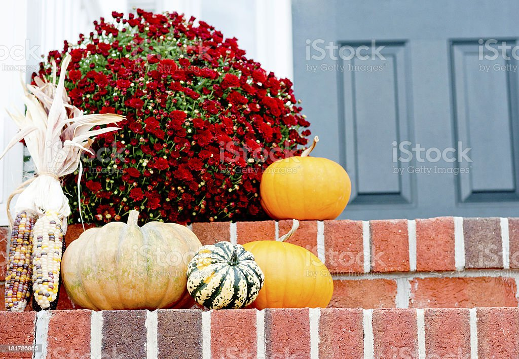 Pumpkins and squash on a front door step stock photo