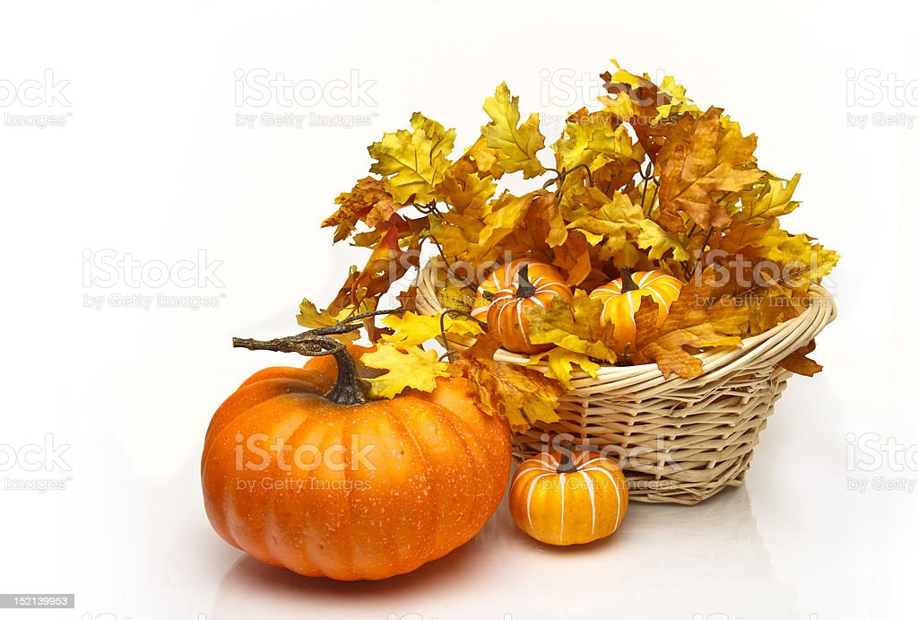 Pumpkins in a wicker basket with fall leaves royalty-free stock photo