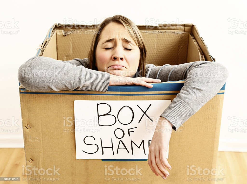 Punishment time! Unhappy woman confined to box of shame stock photo