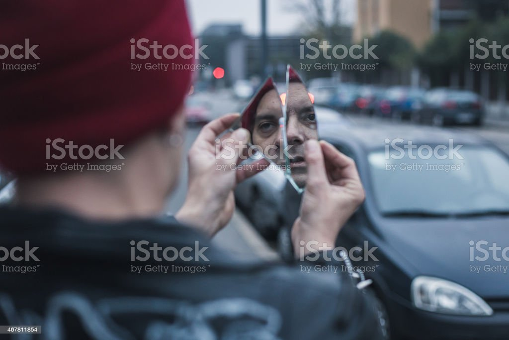 Punk guy looking at himself in a shattered mirror stock photo