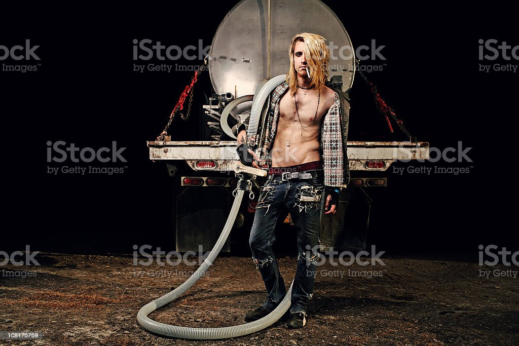 Punk Male Holding Old Water Hose From a Truck royalty-free stock photo