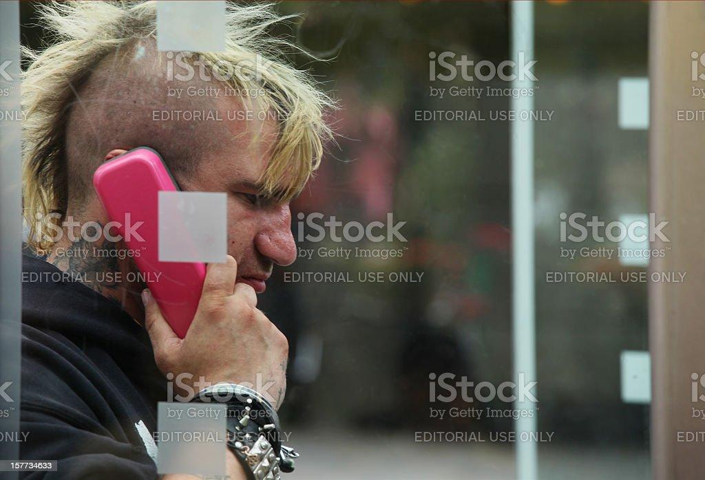 Punk man in Deutsche Telekom telephone box Berlin, Germany stock photo