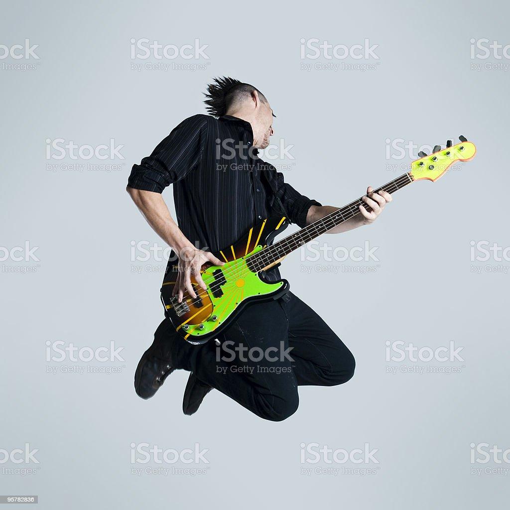 Punk man playing electric guitar in midair stock photo