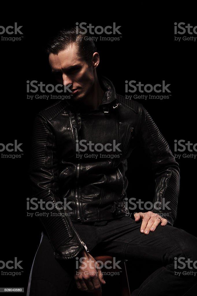 punk model in leather jacket posing seated in dark studio stock photo