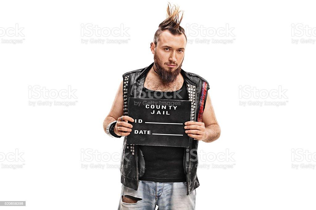 Punk rocker posing for a mug shot stock photo