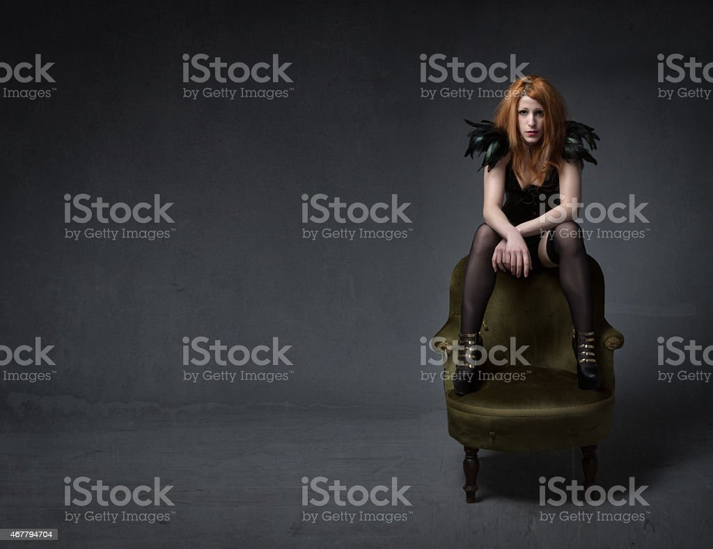punk sitting with foot on sofa stock photo