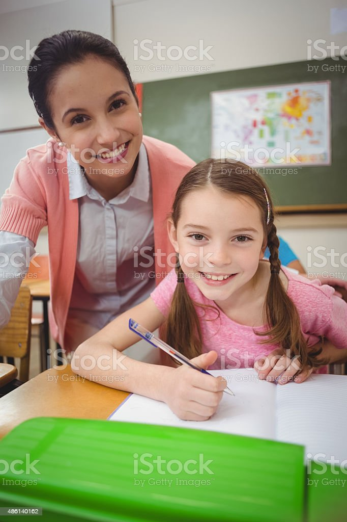 Pupil and teacher at desk in classroom stock photo