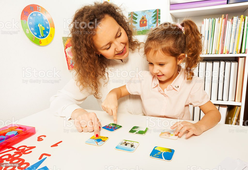 Pupil points to right card with images at the desk stock photo