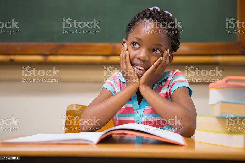 Pupil sitting at her desk stock photo