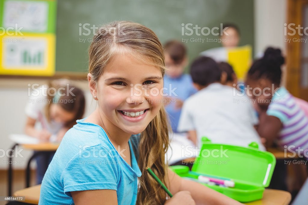 Pupil smiling at camera in classroom stock photo