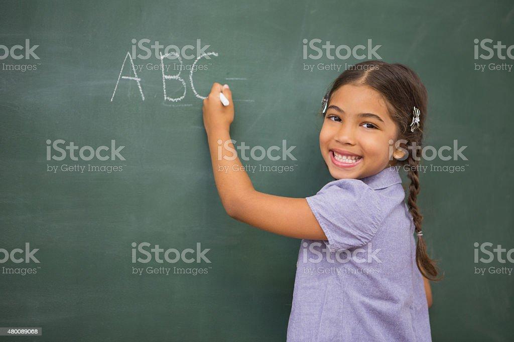Pupil writing on large blackboard stock photo
