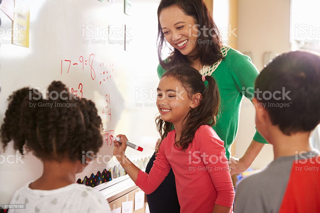 Pupil writing on the board at elementary school maths class stock photo