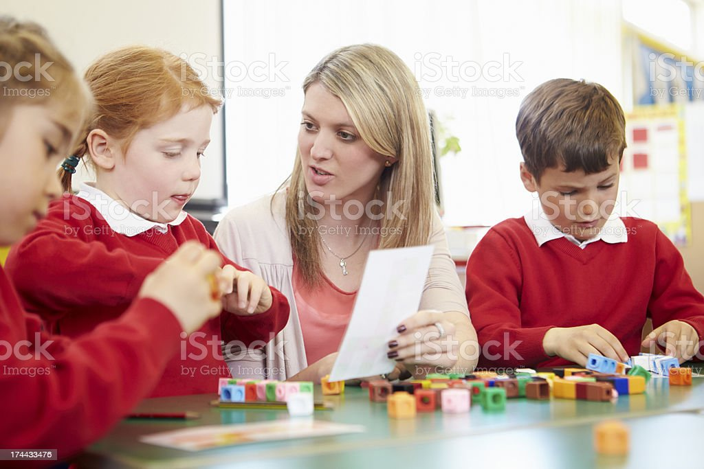 Pupils And Teacher Working With Coloured Blocks royalty-free stock photo