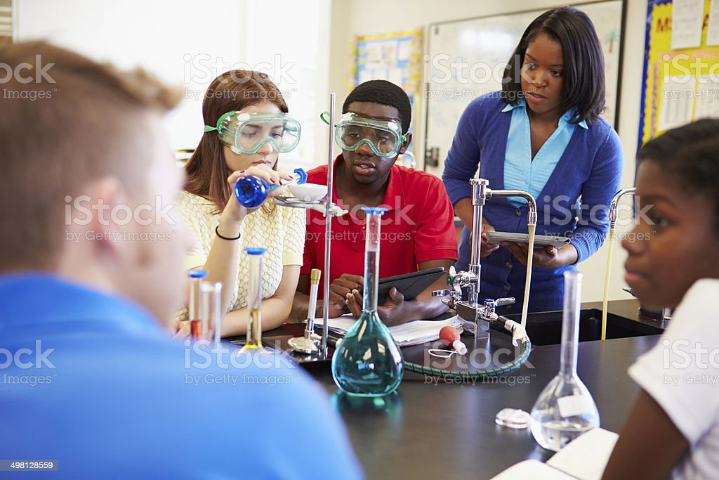 Pupils Carrying Out Experiment In Science Class stock photo