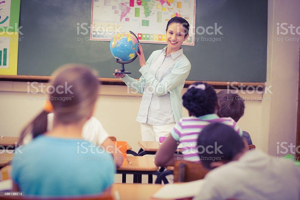 Pupils listening to their teacher holding globe stock photo