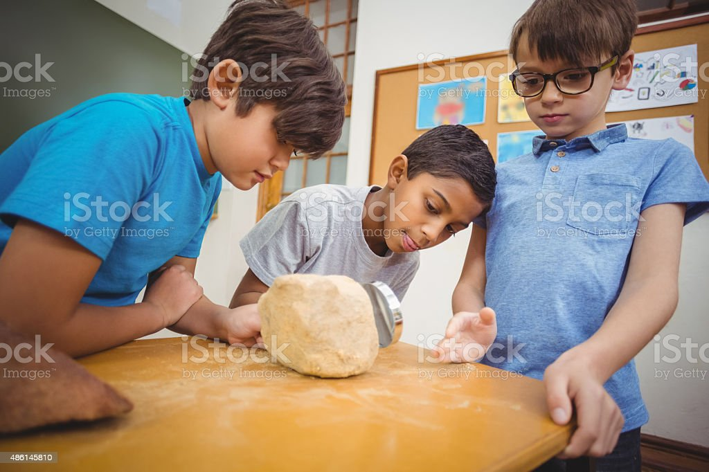 Pupils looking at rock with magnifying glass stock photo