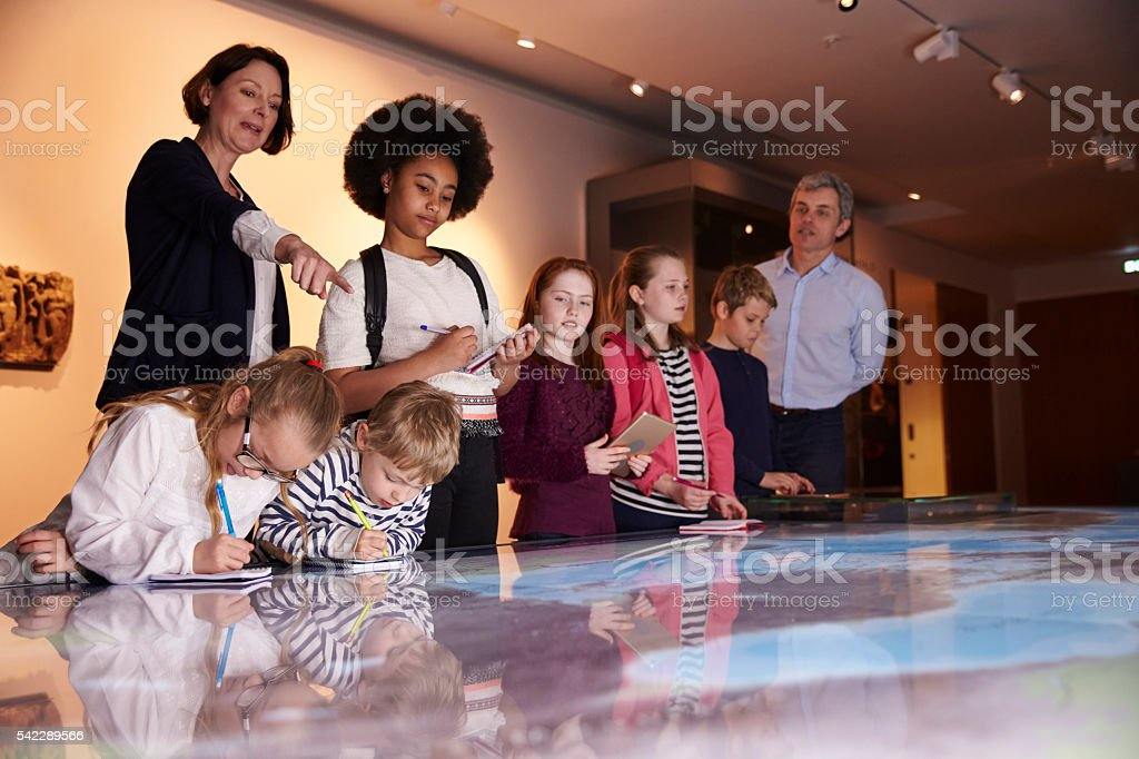 Pupils On Trip To Museum Looking At Map And Making stock photo