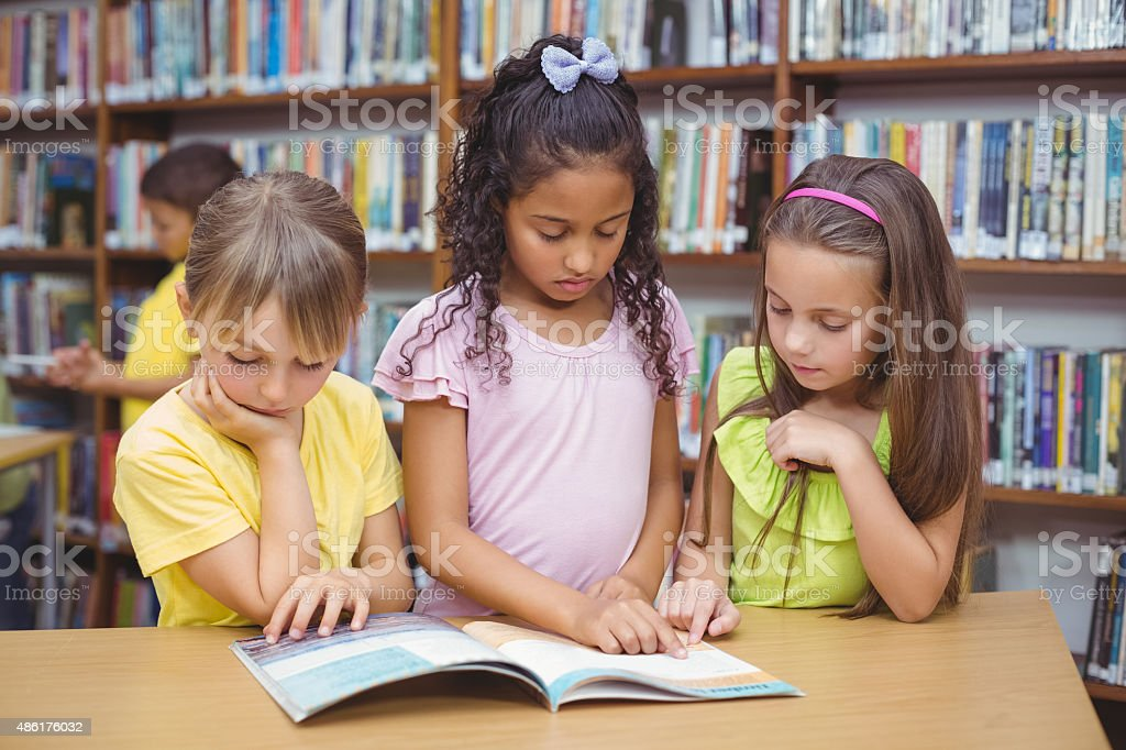 Pupils reading book together in library stock photo