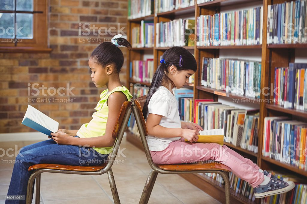 Pupils reading books in the library stock photo