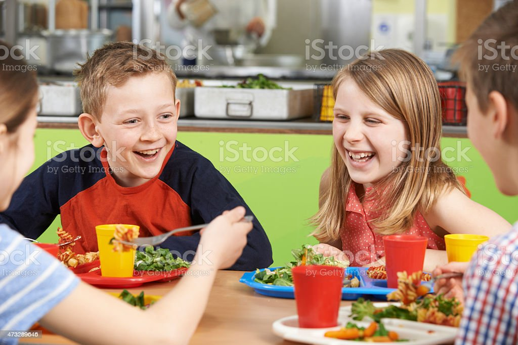 Pupils Sitting At Table In School Cafeteria Eating Meal stock photo