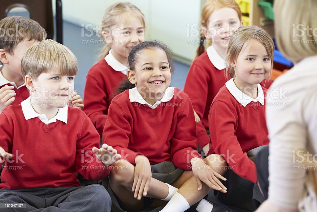 Pupils Sitting On Mat Listening To Teacher royalty-free stock photo