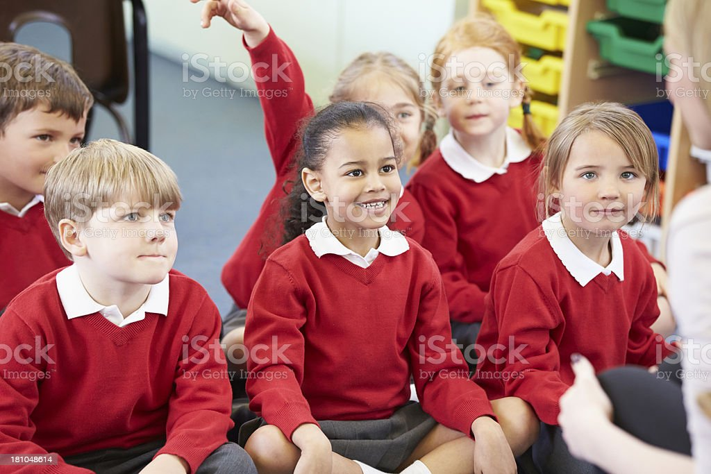 Pupils Sitting On Mat Listening To Teacher royalty-free stock photo