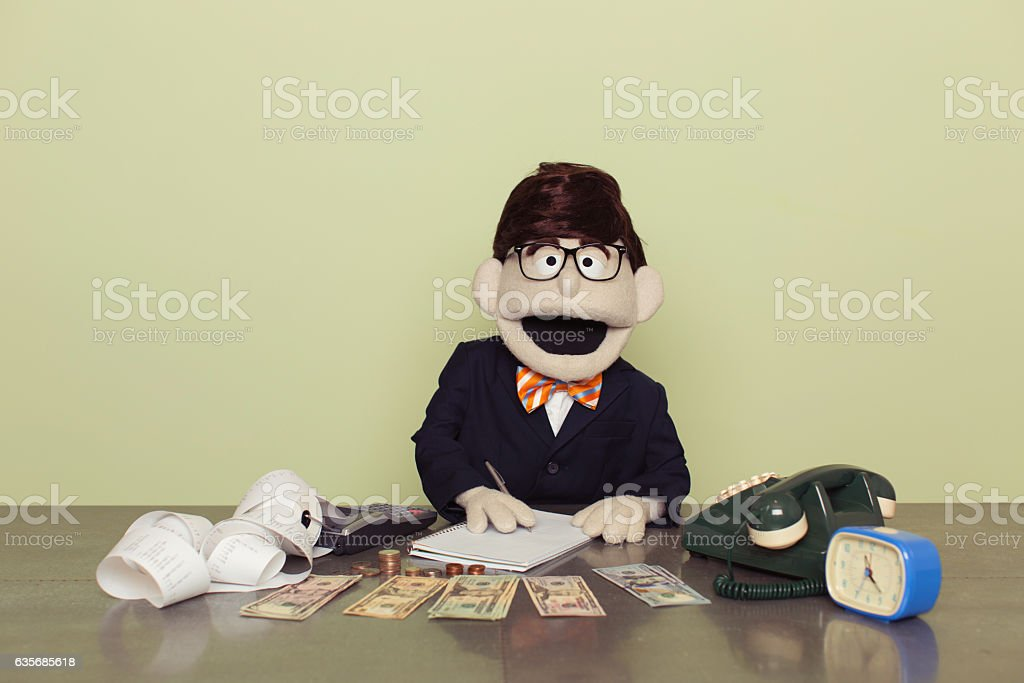 Puppet Accountant Counts American Dollars with Calculator stock photo