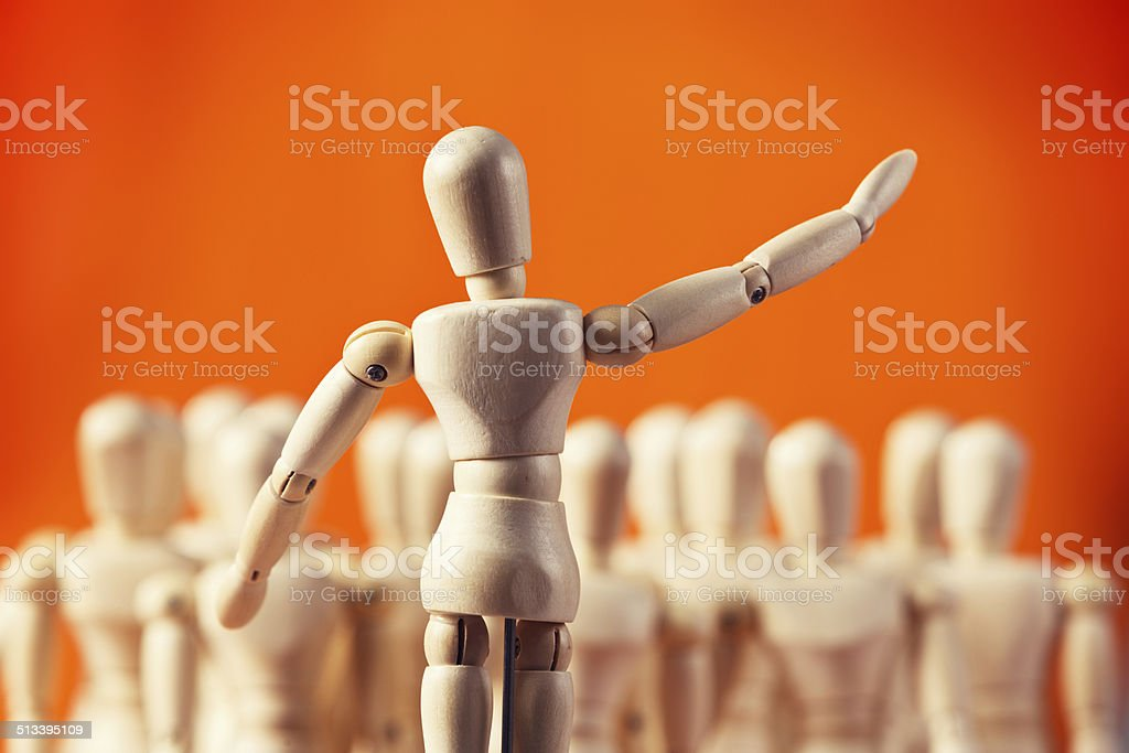 Puppet speaker or conductor addresses crowd of wooden lay figures stock photo