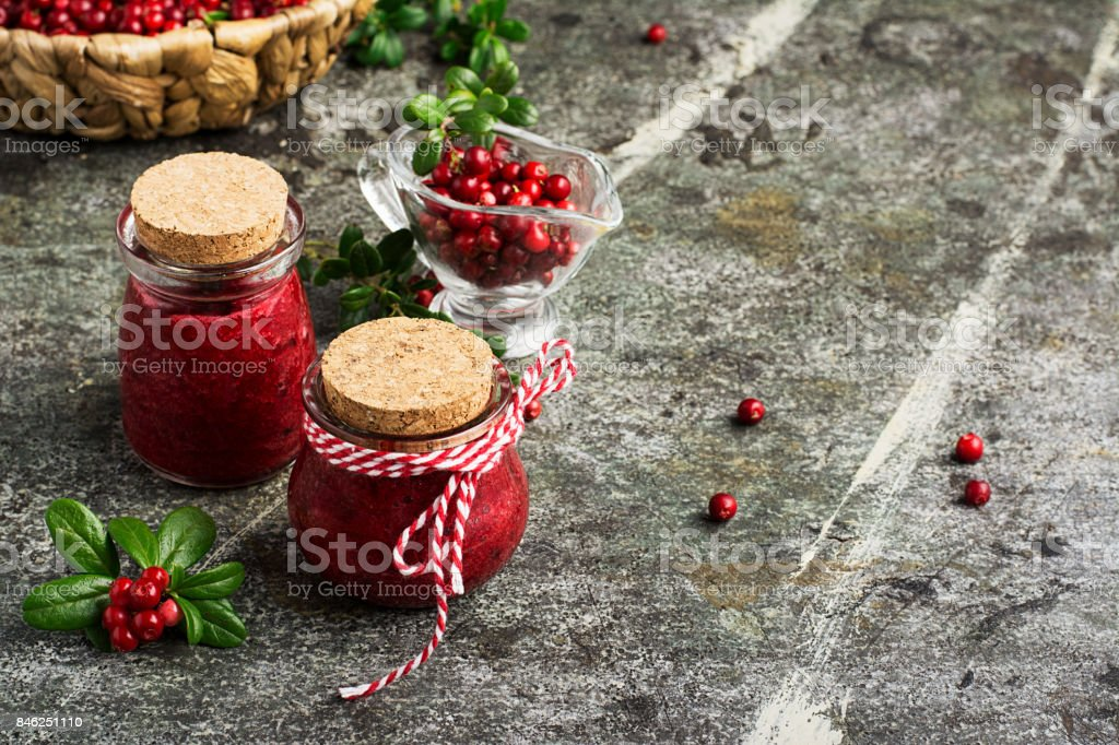 Puree of the northern wild forest cowberry, cranberry for a healthy organic diet in small glass portioned jars with berries and leaves on a gray stone background. Selective focus. stock photo