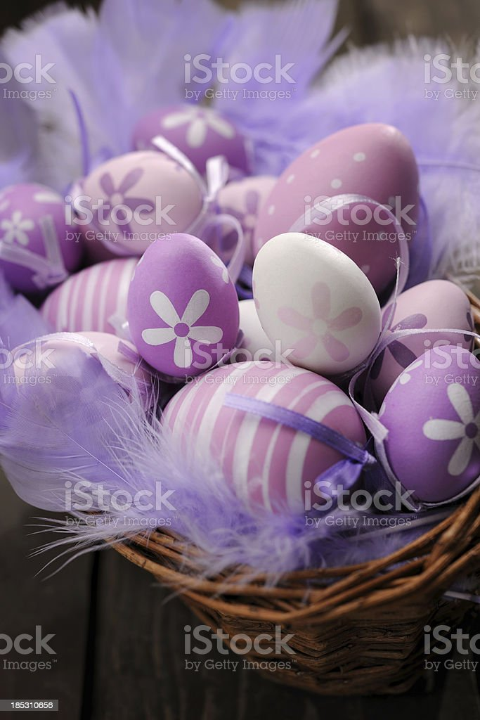 Purple and pink easter eggs in a basket royalty-free stock photo