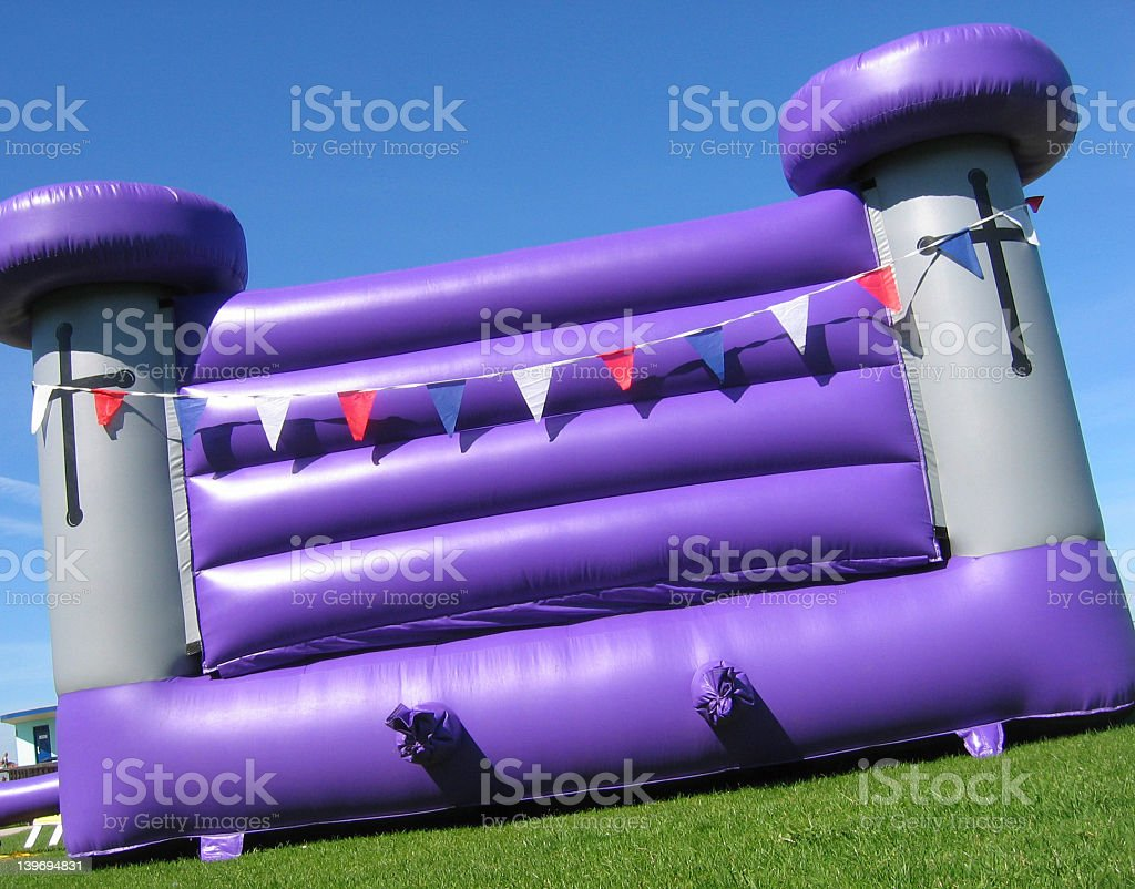 Purple and silver bouncy castle with flags outside stock photo