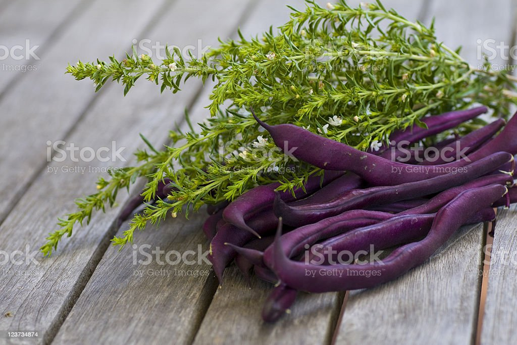 Purple beans lying on a wooden table stock photo