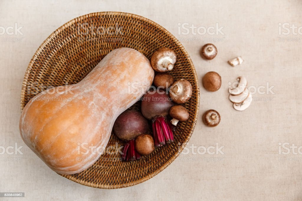 Purple Beets,Orange Pumpkin,Fresh Mushrooms in the Rattan Braided Big Plate,on the Linen Tablecloth.Autumn Garden's Vegetable Background.Top View. stock photo
