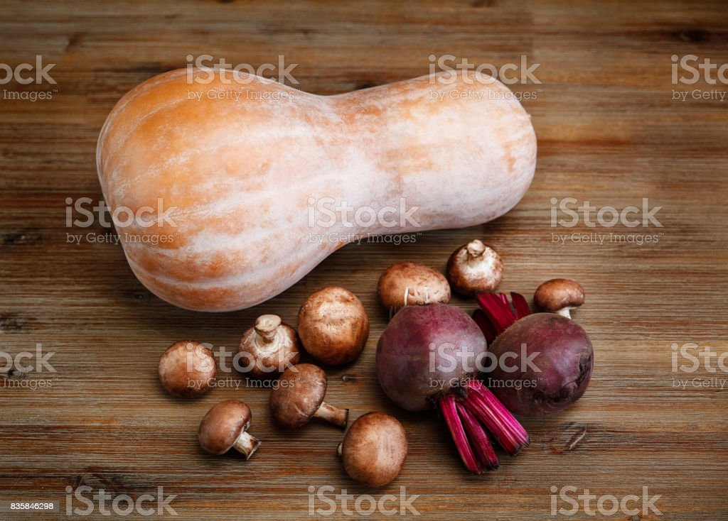 Purple Beets,Pumpkin,Fresh Mushrooms on the Wooden Table.Autumn Garden's Vegetable Background.Top View. stock photo