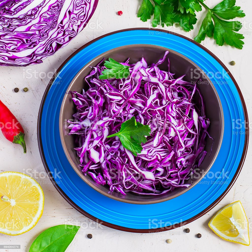 Purple cabbage salad and ingredients on a bright background. stock photo