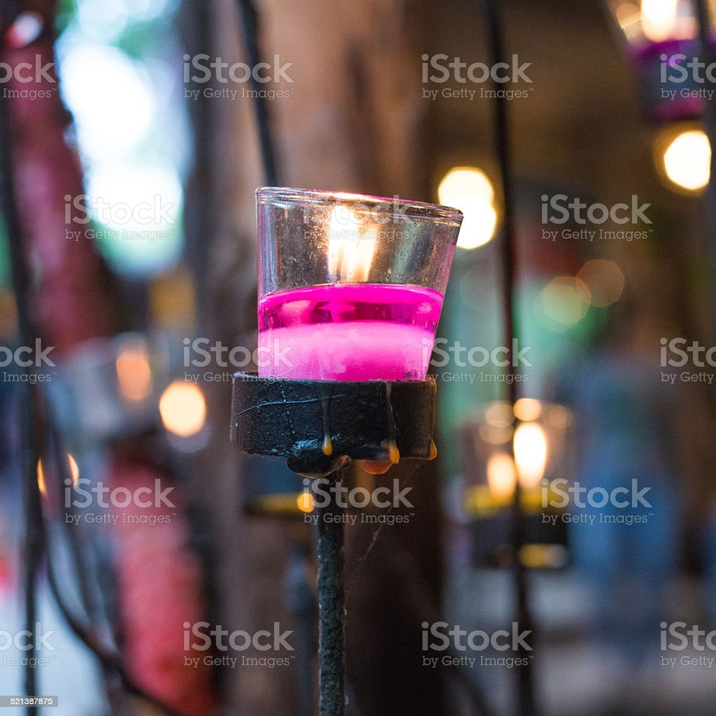 Purple candle in glass with bokeh stock photo
