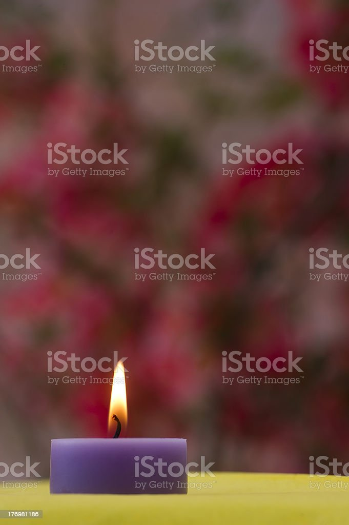 Purple candle on yellow stock photo