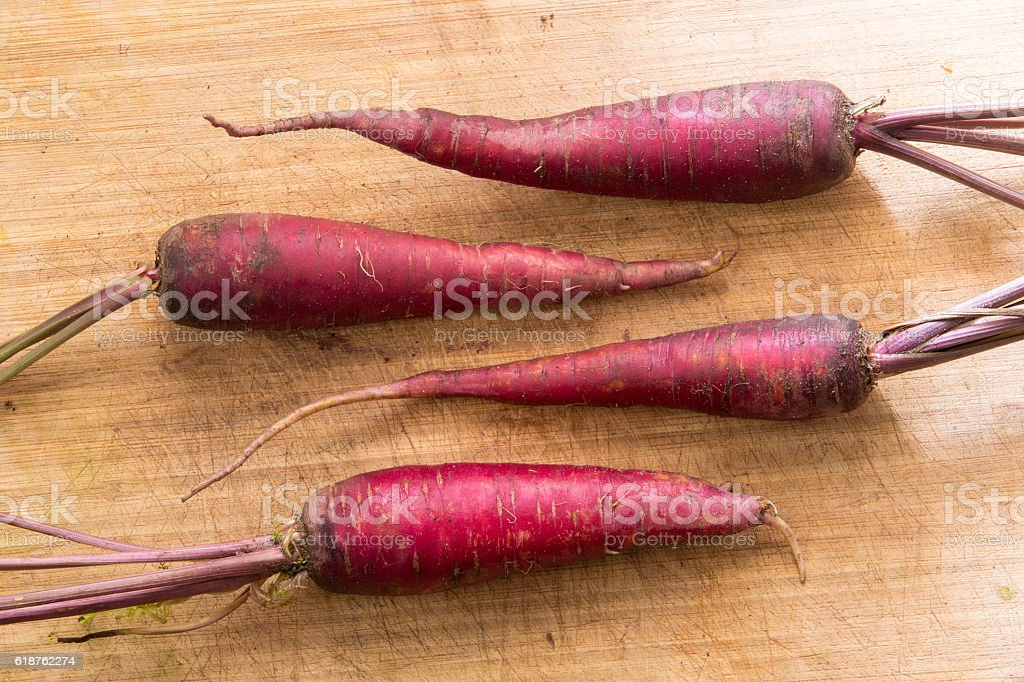 Purple Carrots on Wood counter stock photo