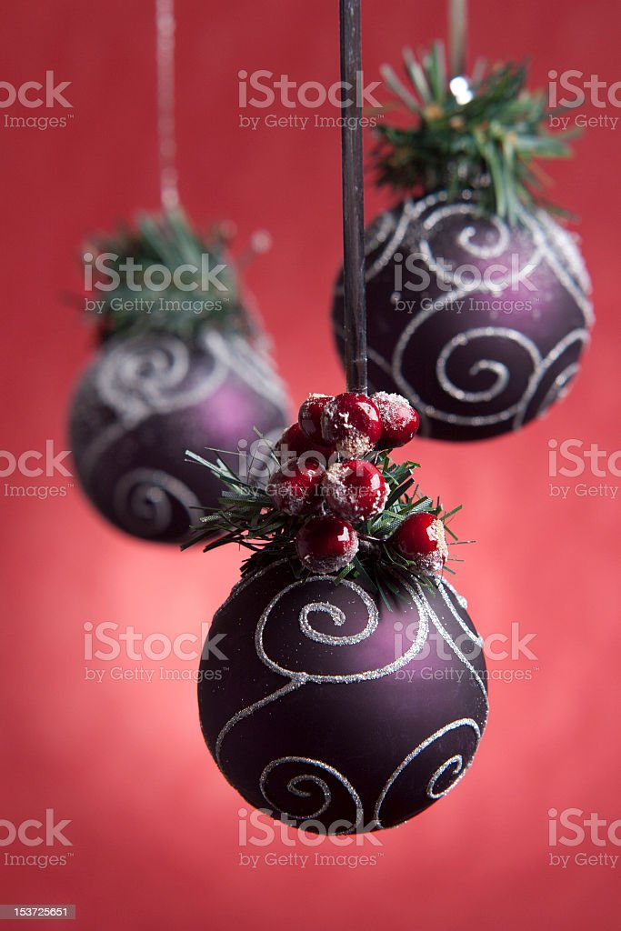 purple christmas balls on red background with berrys and acorns stock photo