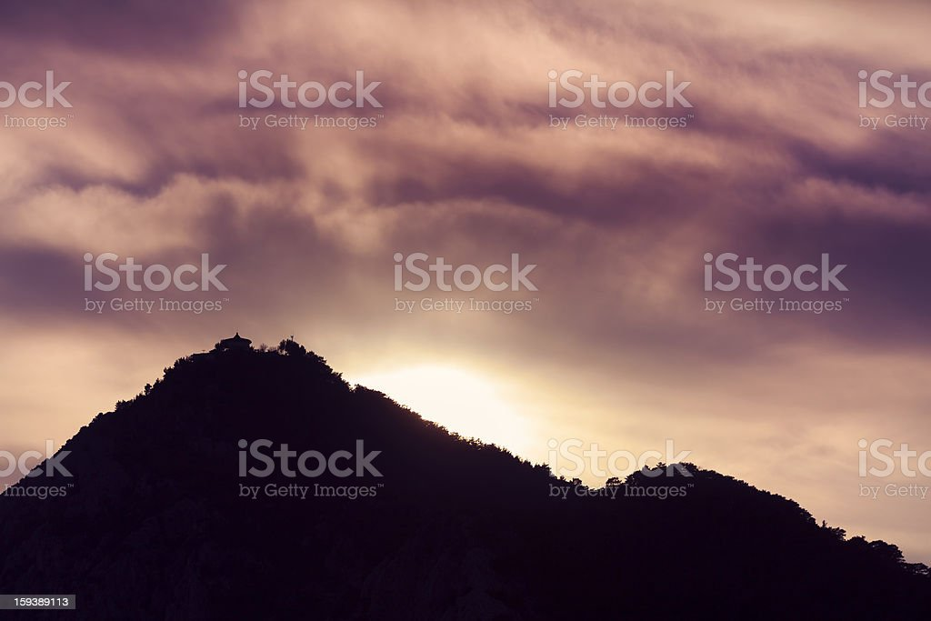 Purple Clouds and Back lit mountain stock photo