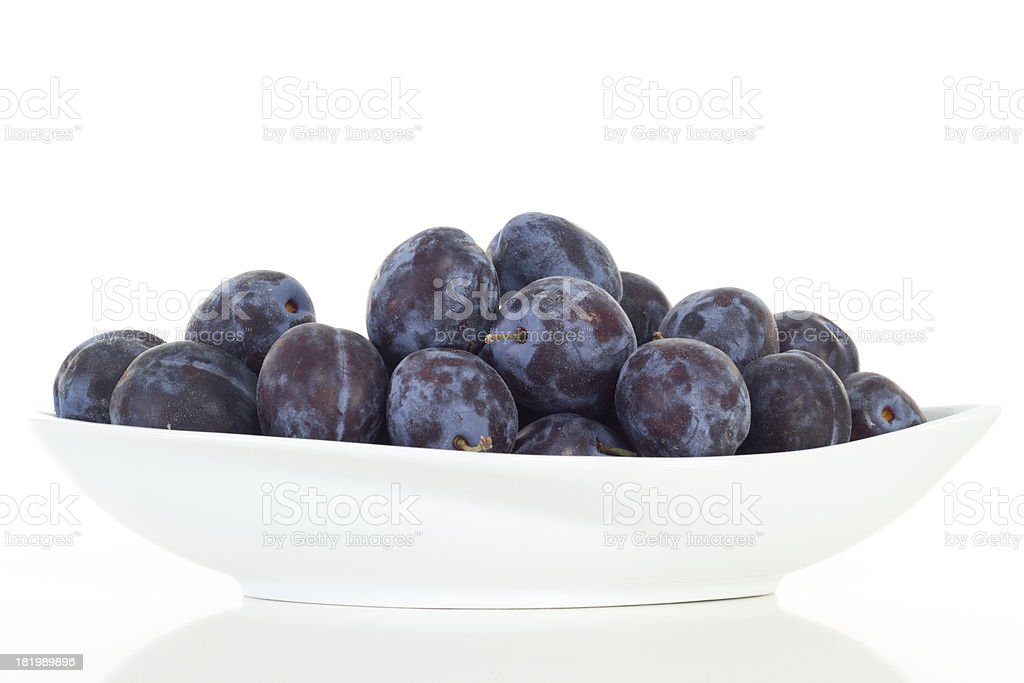 Purple colored plums in white dish royalty-free stock photo