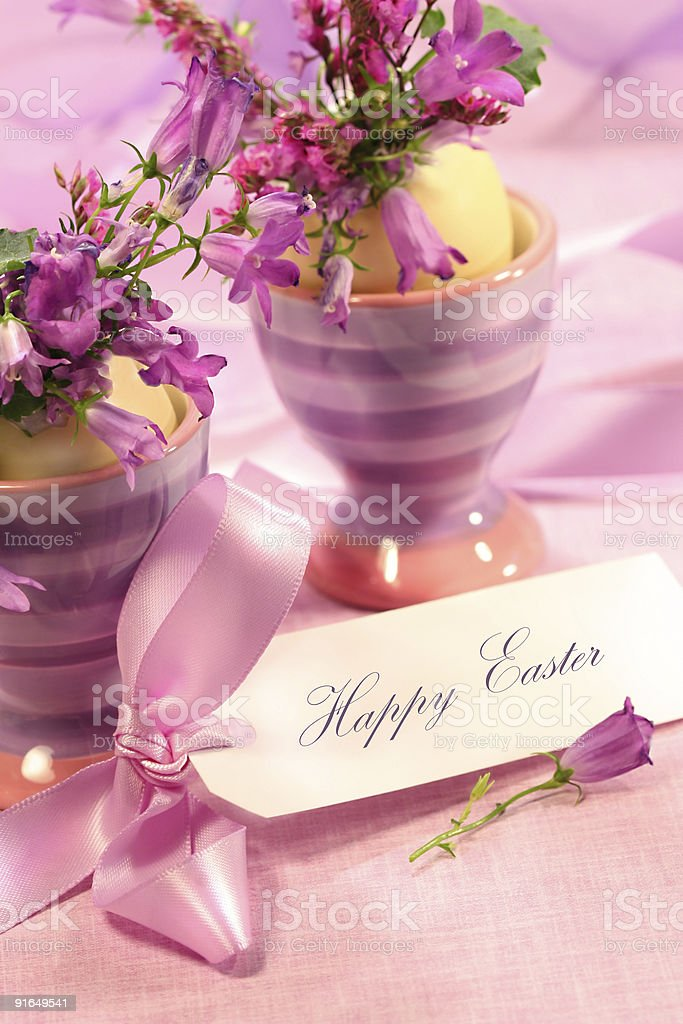 Purple flowers in eggs cups stock photo