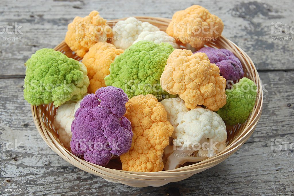Purple, green, yellow and white cauliflower in a bowl stock photo