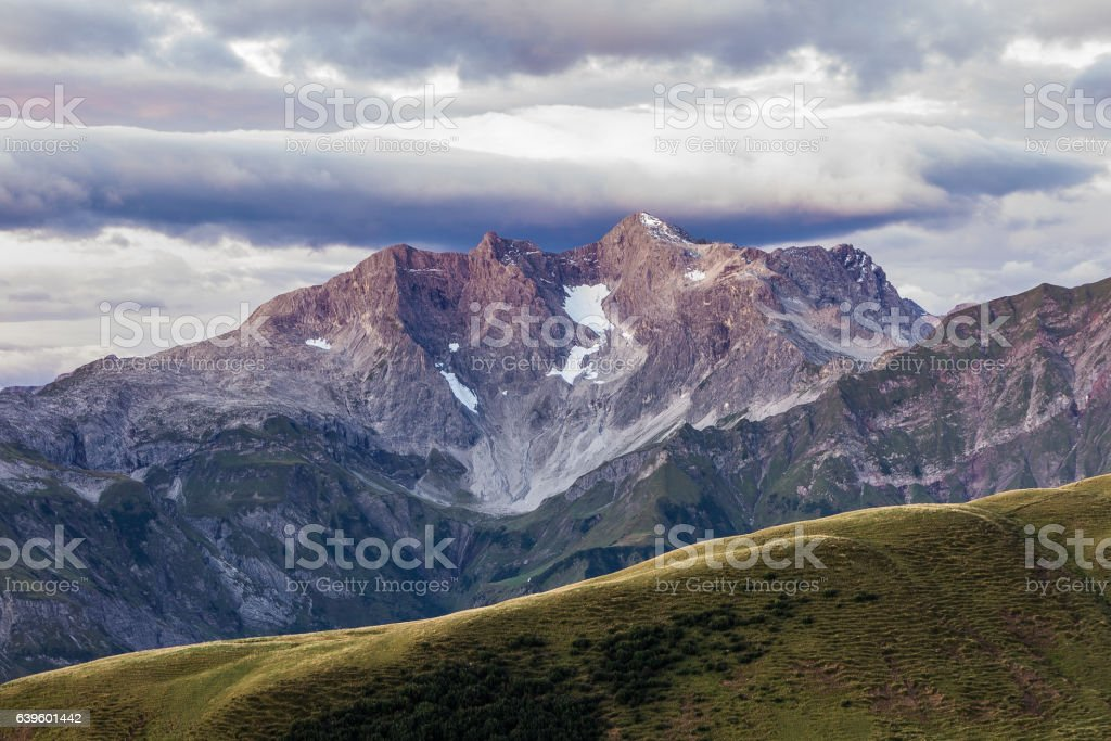 Purple light illuminates a big mountain and the moody sky stock photo